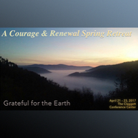 The 2016 Courage And Renewal poster backgound is a photo of a lake with a layer of mist above. We see it from afar through a chasm in the dark wooded hills at sunrise or sunset.